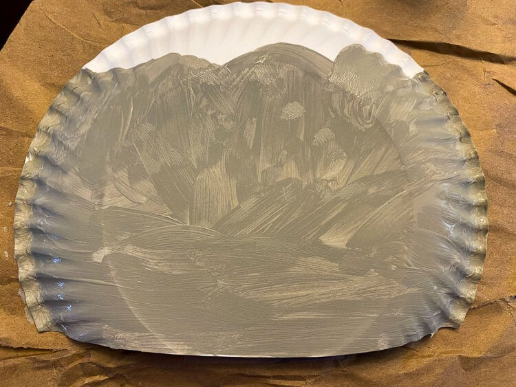 Mountains painted grey on the paper plate.