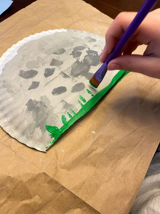 Painting grass on the bottom of the paper plate.