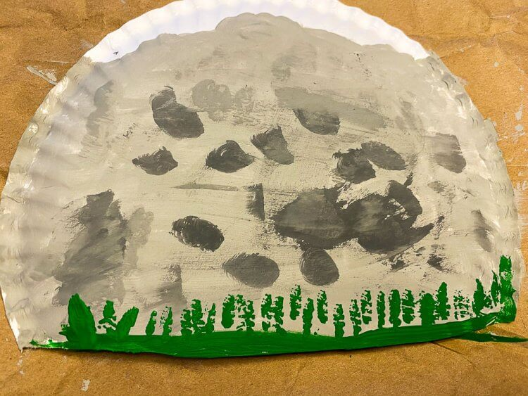 Complete paper plate with mountains, rocks and grass.