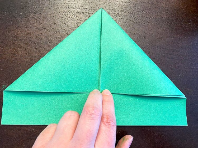 Folding in the two corners of the construction paper.
