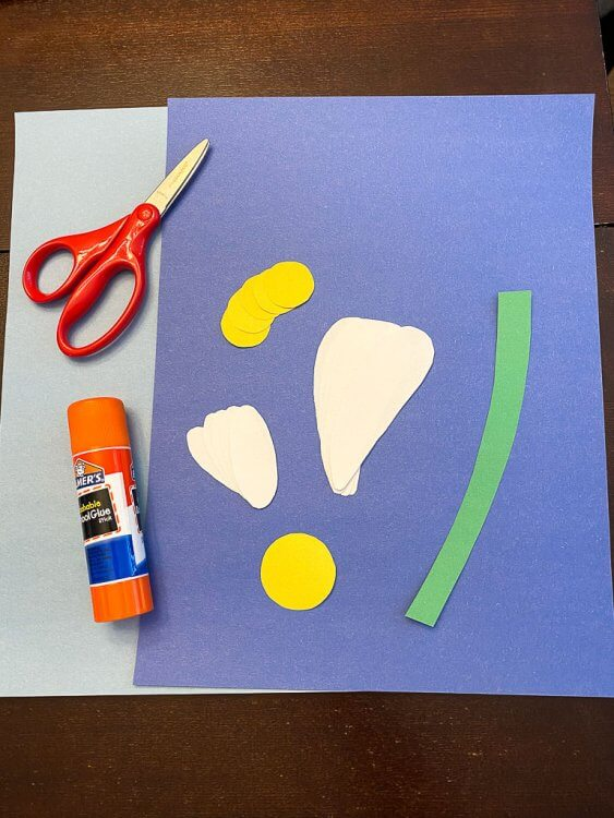 Project supplies: light blue and dark blue construction paper, glue, scissors, one green stem, five large white petals, five small white petals, five small circles and one large yellow circle.