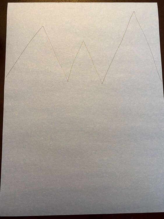 Drawing a mountain shape on the light blue paper.