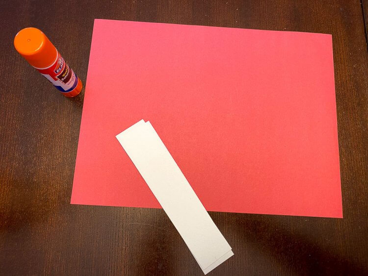Red construction paper with two white strips and glue.