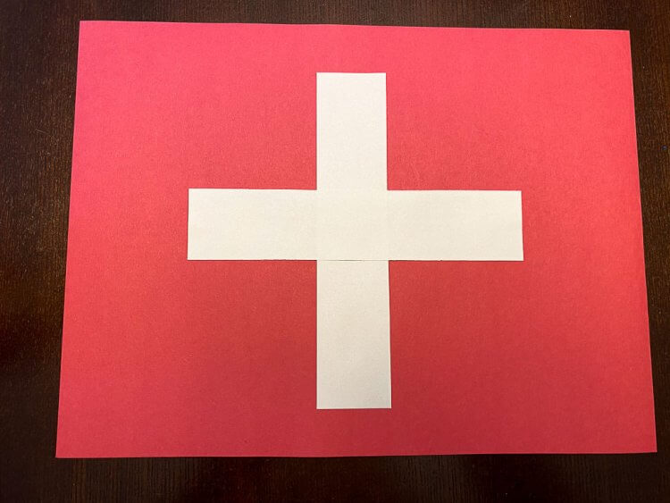 Laying the two pieces of white strips of paper in a cross shape in the center of the red construction paper to make the swiss flag.