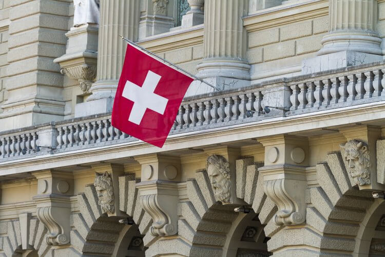 Swiss flag hanging from a stone building. It's a red flag with a white cross in the center.