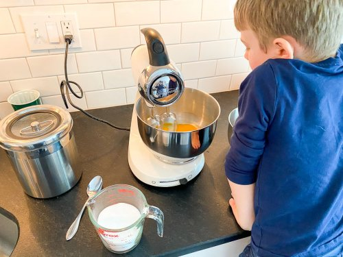 Getting ready to add flour into the mixer with a little boy watching the process.
