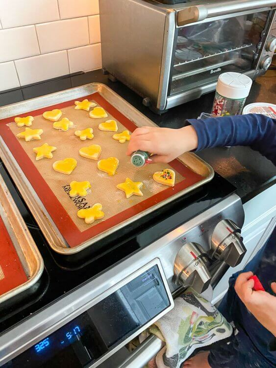 Cut cookies in various shapes on a cookie sheet with a little boy adding sprinkles.