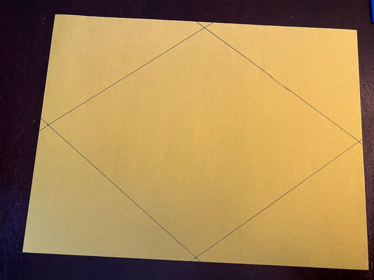 Drawing a rhombus on a yellow piece of construction paper to make the flag of Brazil.
