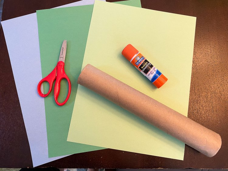 Blue, green and lime colored construction paper with scissors, glue and an empty paper towel roll.