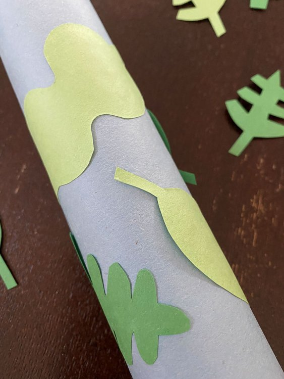 Gluing leaves to the blue paper on the paper towel roll.
