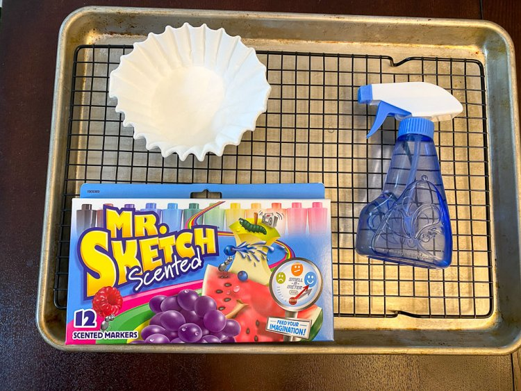 White cupcake liners, water spray bottle and Mr. Sketch markers on a cookie drying rack over a cookie sheet.
