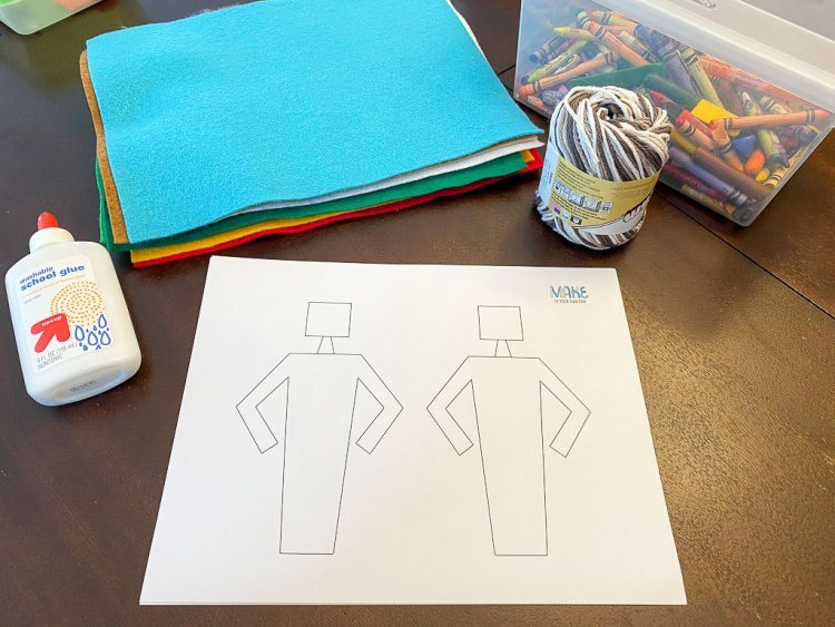 Laying out the supplies: felt, yard, glue, crayons, body shapes on a white piece of paper.