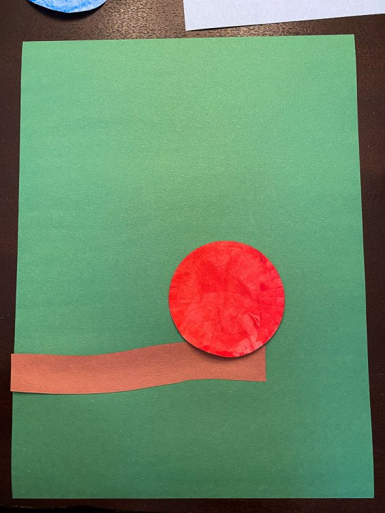 Gluing a red cupcake liner to the branch.