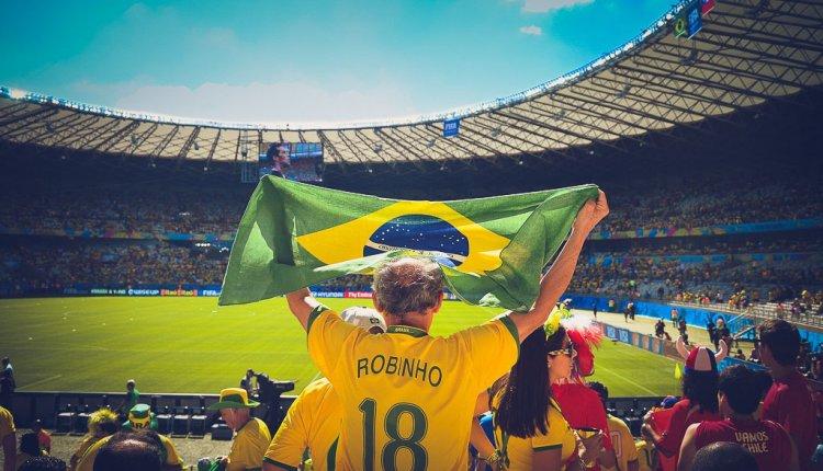 Soccer fan holding up the flag of Brazil.