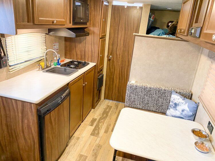 Interior view of a small travel trailer with a kitchen, small seating area and bathroom in the rear.