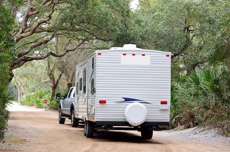 Looking at the back of a travel trailer style RV driving down the road with trees on each side of the road.