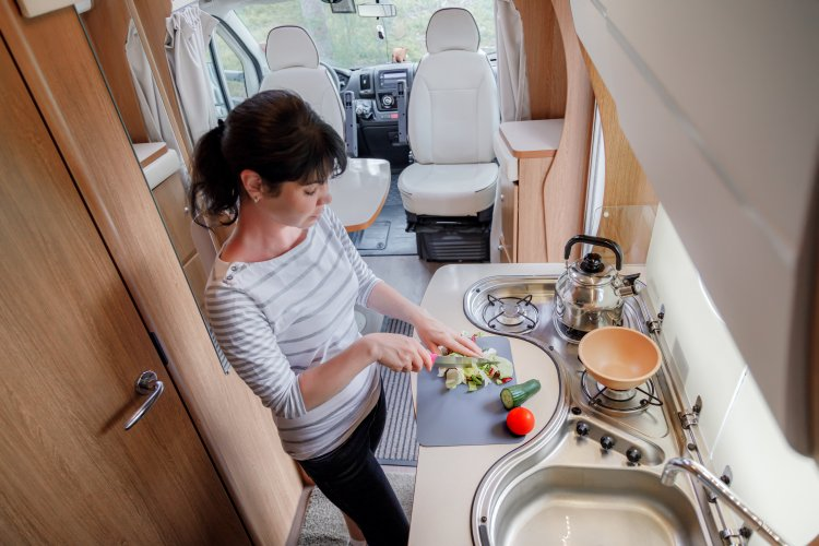 Woman cooking in camper, motorhome RV interior. Family vacation travel, holiday trip in motorhome, Caravan car Vacation.